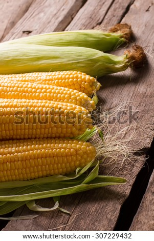 Delicious corn cobs on a vintage wooden background. Corn with leaves. - stock photo