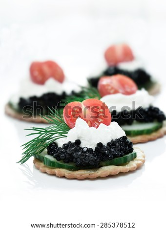 Delicious cream cheese, cucumber and caviar canapes against white. Copy space. - stock photo