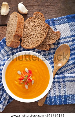 Delicious cream of pumpkin soup in a bowl on wooden table - stock photo