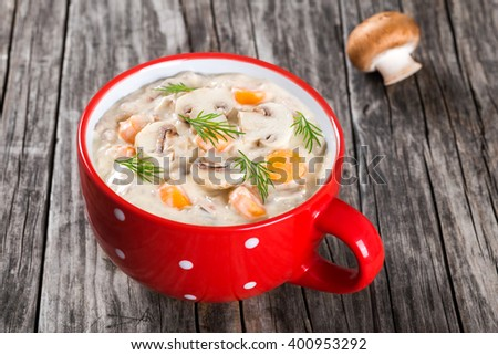 Delicious creamy cheese mushroom soup with spring carrots and veggies, decorated with dill, in a red cup on an old rustic table, horizontal close-up - stock photo