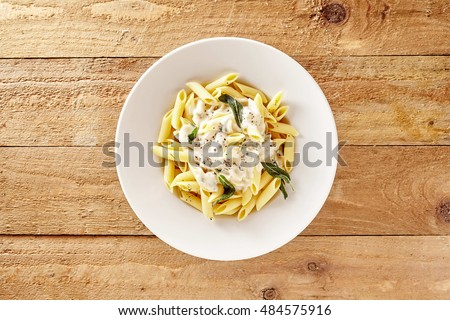 Delicious creamy Italian penne pasta starter with pepper seasoning and fresh basil viewed from above on rustic wooden centered with copy space