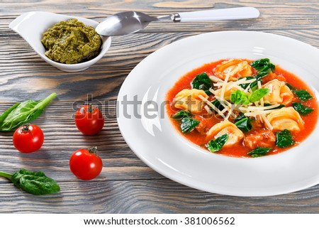 Delicious creamy tomato soup with tortellini, italian sausages, spinach, and vegetables decorated with basil leaves in a wide rim white plate on a wooden table, pesto sauce in a gravy boat, close-up - stock photo