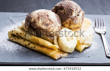 Delicious crepes filled with chocolate sauce, with ice cream scoops on top, elegant tasty dessert dish serving