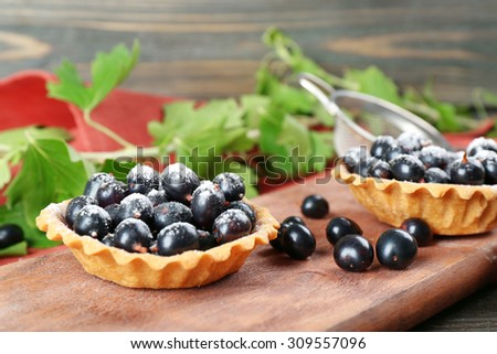 Delicious crispy tarts with black currants on wooden cutting board, closeup - stock photo