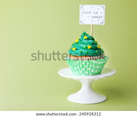 Delicious cupcake with inscription on green background - stock photo