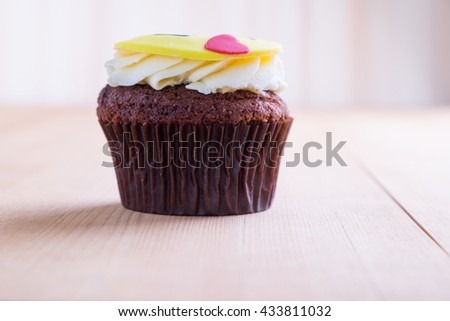Delicious cupcake with smiley icon on it on wooden desk
