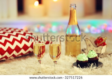 Delicious cupcakes and champagne on home interior background  - stock photo