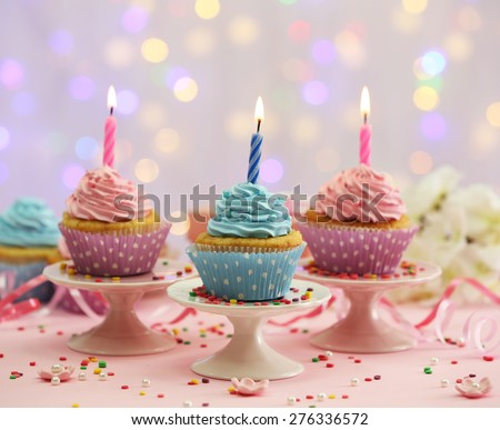 Delicious cupcakes on table on light background - stock photo