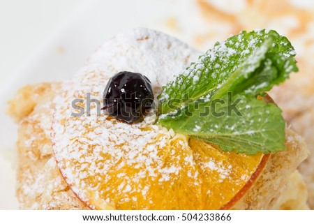 Delicious custard cake with orange and mint. Macro. Photo can be used as a whole background.