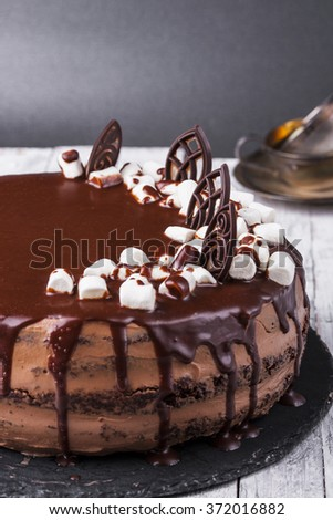 Delicious dark chocolate cake in white plate on wooden table background - stock photo