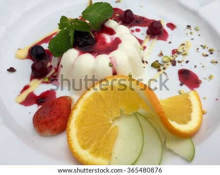 Delicious desserts with sliced oranges and green apple on the white plate - stock photo