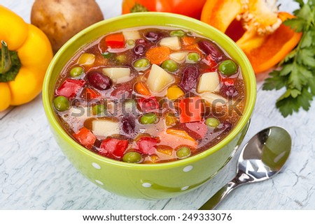 Delicious diet vegetarian soup on the table. Against the background of tomatoes and basil leaves - stock photo