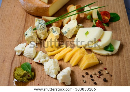 delicious Different types of cheese laid out on a wooden Board - stock photo