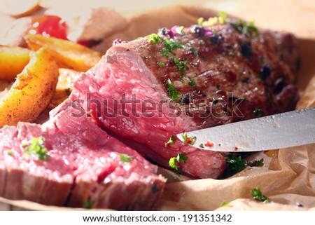 Delicious dinner of savory rare roast beef cooked with fresh herbs and potato wedges being carved for serving - stock photo