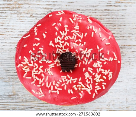Delicious donut with icing on wooden background - stock photo