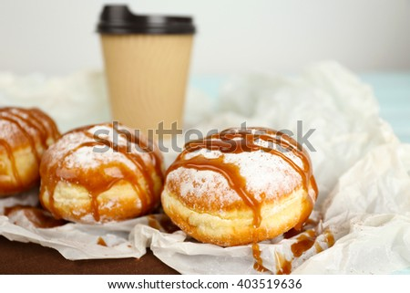 Delicious donuts with caramel on parchment closeup - stock photo