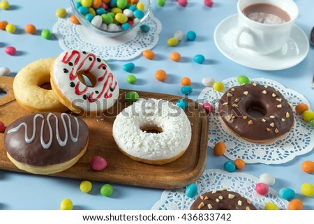 Delicious donuts with chocolate, coconut and strawberry. Served on the wooden board and white napkin. Decorated with multicolored candy and cup of coffee. Blue background. Horizontal image.  - stock photo