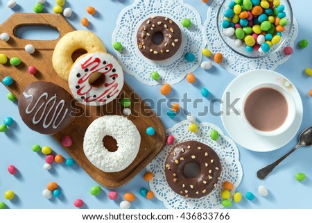 Delicious donuts with chocolate, coconut and strawberry. Served on the wooden board and white napkin. Decorated with multicolored candy and cup of coffee. Blue background. Horizontal image. Top view.  - stock photo