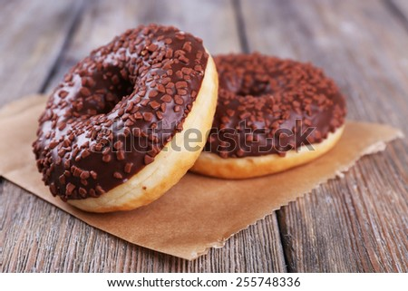 Delicious donuts with icing and chocolate crumb on wooden background - stock photo