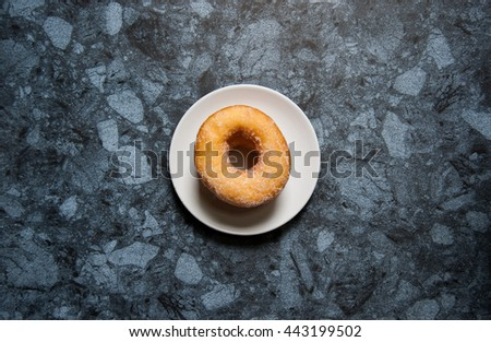 Delicious donuts with icing and cup of milk in plate on black marble table.
