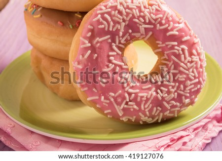 Delicious donuts with icing on green plate - stock photo