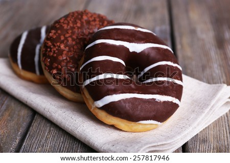 Delicious donuts with icing on napkin on wooden background - stock photo