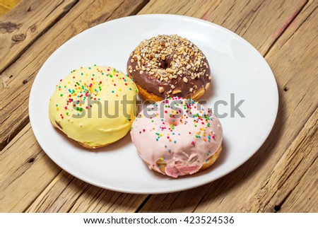 Delicious donuts with icing on plate  - stock photo