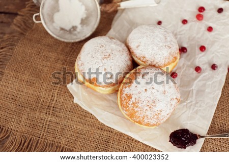 Delicious donuts with jam on parchment and sackcloth closeup