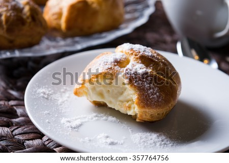 Delicious eclair with cream and powdered sugar on a plate. horizontal, close up