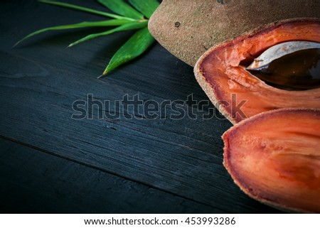 Delicious exotic cutted fruit Sapodilla on wooden board, free copyspace, focus in the center of table