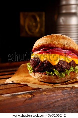 Delicious fast food cheeseburger with melted cheese on a beef patty with salad trimmings served on brown paper on a wooden counter, with copy space