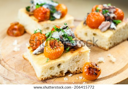 Delicious focaccia with sardines and cherry tomatoes on wood - stock photo
