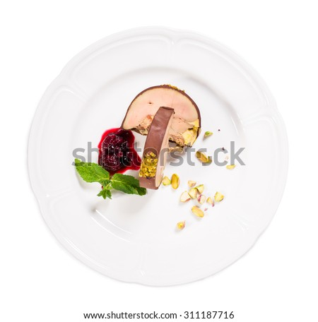 Delicious foie gras covered with dark chocolate and pistacchio nuts with red berry jam and mint. Isolated on a white background. - stock photo