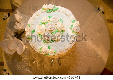 Delicious four tier wedding cake with yellow roses, green leaves and sweet white icing.