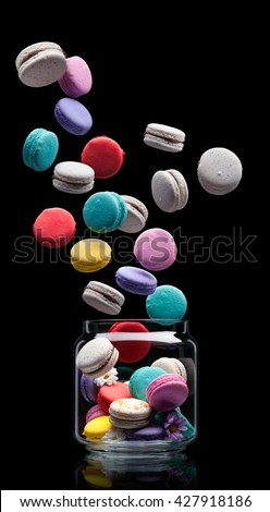 delicious French dessert macarons flying out from the glass jar on a black background - stock photo