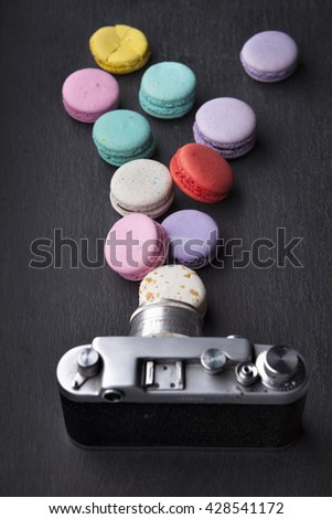 delicious French dessert macarons with vintage camera on a black background - stock photo