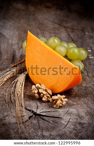 Delicious french yellow cheese on wooden table - stock photo