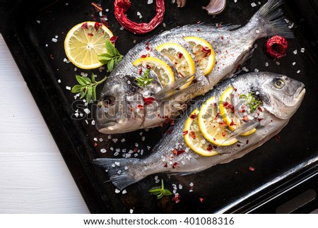 Delicious fresh bream or dorade fish on dark background. Fish with aromatic herbs, lemon, garlic, spices and vegetables - healthy food, diet or cooking concept - stock photo