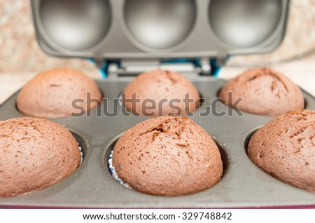 Delicious fresh chocolate cupcakes straight out of oven still sitting inside metal pan, shot from side sligthly above angle. - stock photo