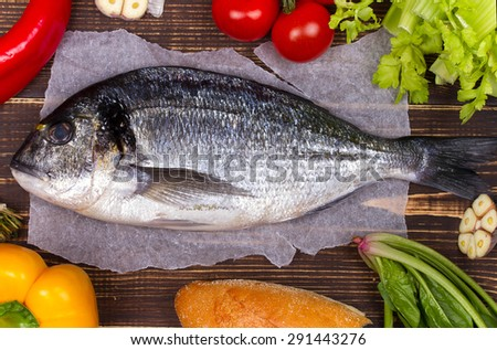 Delicious fresh fish and vegetables on dark vintage background; view from above, studio shot - stock photo