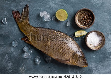 Delicious fresh fish (carp) on dark vintage background for healthy food, diet or cooking concept, selective focus - stock photo