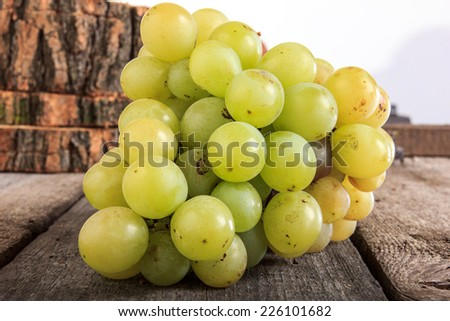 Delicious fresh green grapes on wooden background - stock photo