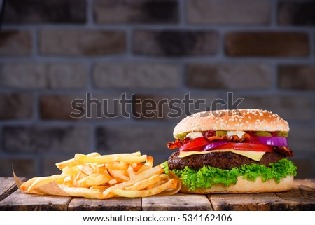 Delicious fresh hamburger with french fries on wooden table. Big burger in classic american style with hot grilled patty with melted cheese on top, tomato, onion, sauces and fried chips.