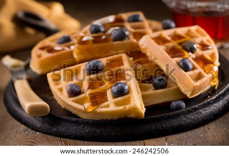 Delicious fresh homemade blueberry waffles with fresh blueberries and maple syrup. - stock photo