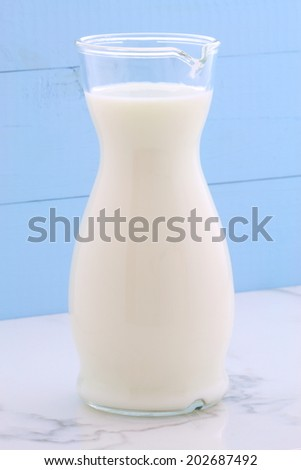 Delicious fresh milk, one of the primary sources of nutrition on vintage Italian carrara marble, farm styling kitchen. - stock photo