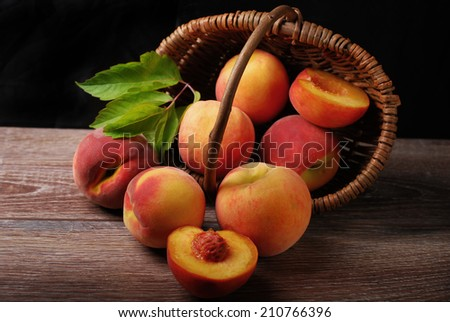 delicious fresh peaches falling out of a wicker basket on wooden background - stock photo