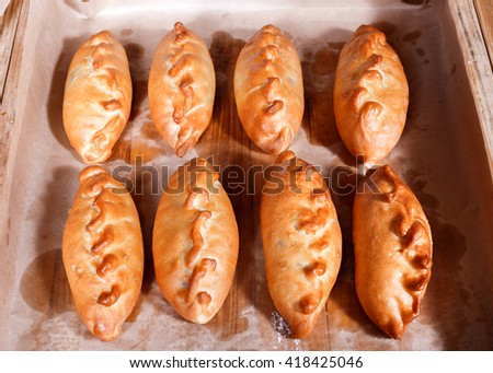 Delicious fresh pies and buns with meat and vegetables on shelf in Bakery shop. Pastries and bread in a bakery - stock photo
