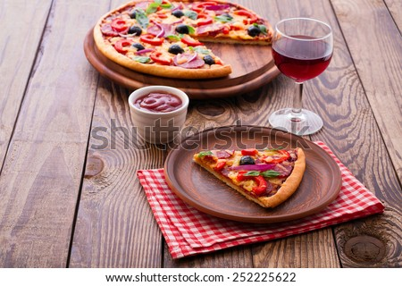 Delicious fresh pizza with ham, salami, tomato, pepper and olives served on wooden table. selective focus, blurry background - stock photo