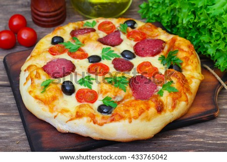 Delicious fresh pizza with salami, tomato and olives served on wooden table.