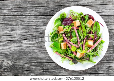 delicious fresh salad of salami and mixed lettuce leaves - baby spinach, arugula, chard in a white dish on an old wooden table, top view - stock photo